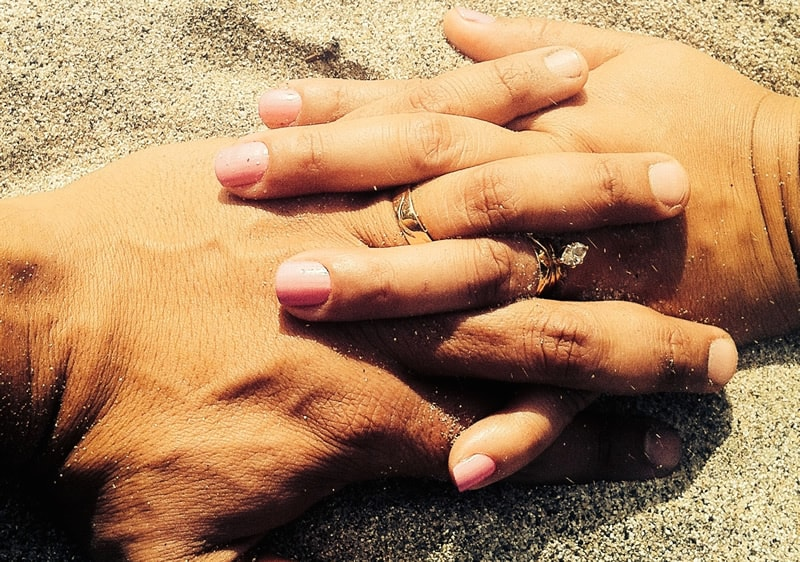 couple-with-hands-entwined-showing-wedding-rings